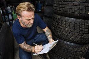 starsi pan zapisuje informacie o pneumatikach na sklade